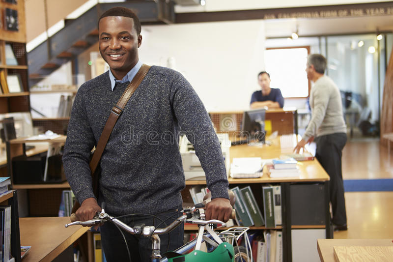 Arkitekt Arrives At Work på cykeln som skjuter det till och med kontor royaltyfri fotografi