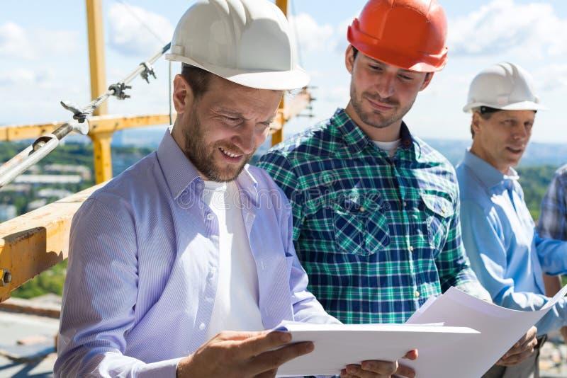 Arkitekt And Builders Looking på den bärande hardhaten för Buiding planritning, medan möta på konstruktionsplats royaltyfri foto