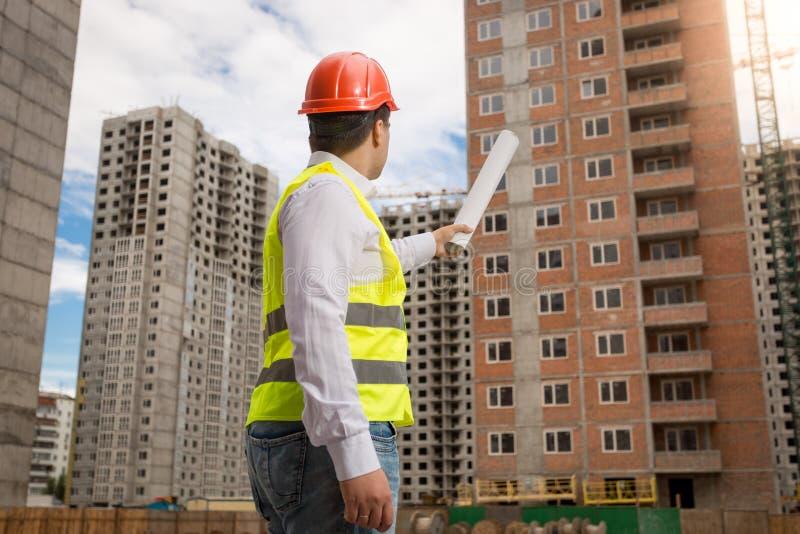 Arkitekt i hardhat och säkerhetsväst som pekar byggnad med rulle arkivbild