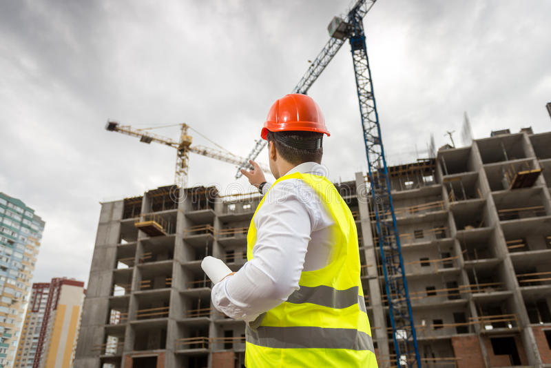 Arkitekt i hardhat som pekar på byggnad under konstruktion arkivbilder