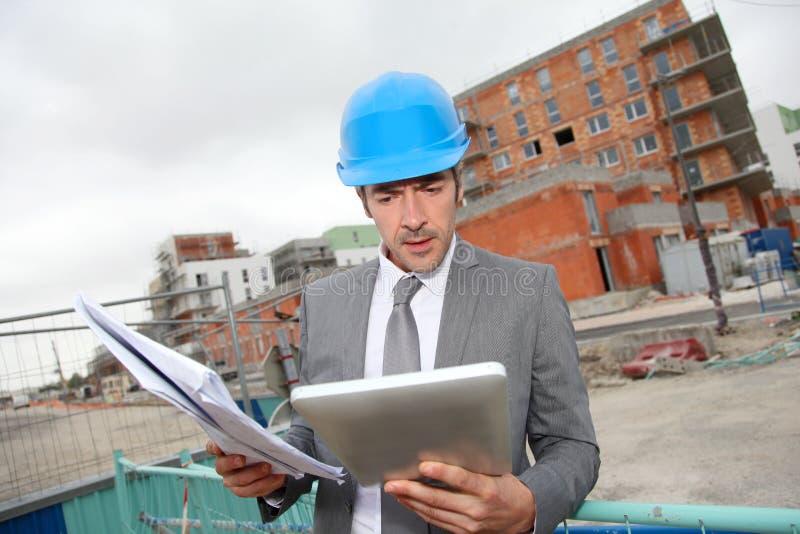 Arkitekt med konstruktionsplan och minnestavla på byggnadsplats royaltyfria foton