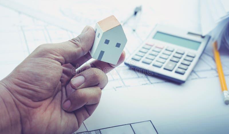 Arkitekt med modellen för litet hus förestående och plandesign Begrepp royaltyfria foton