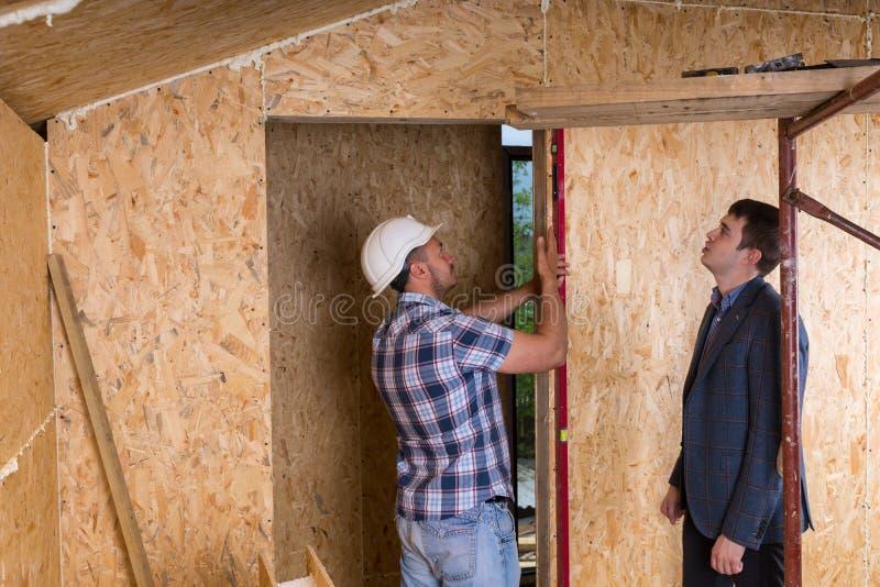 Arkitekt och arbetare som kontrollerar nivåer på dörrram fotografering för bildbyråer