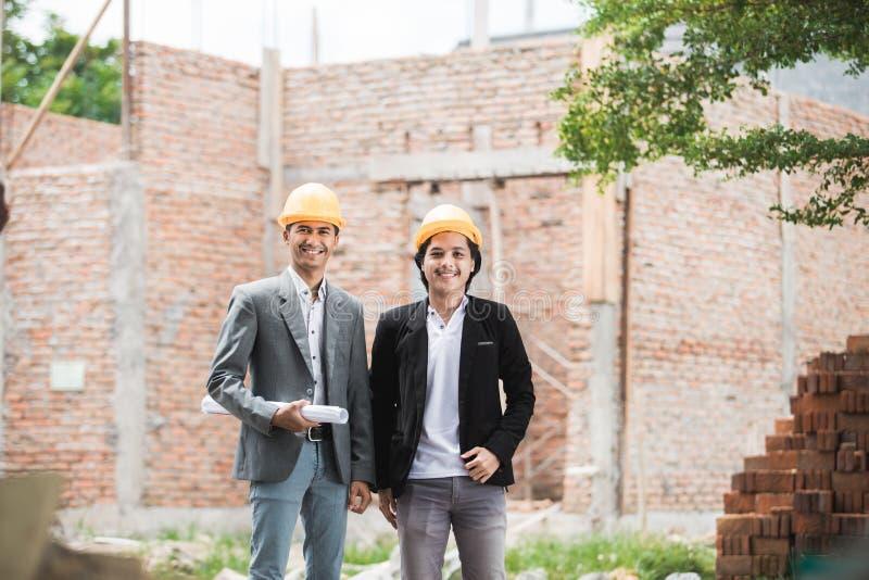 Arkitekt och byggmästare som framme står av oavslutat hus fotografering för bildbyråer