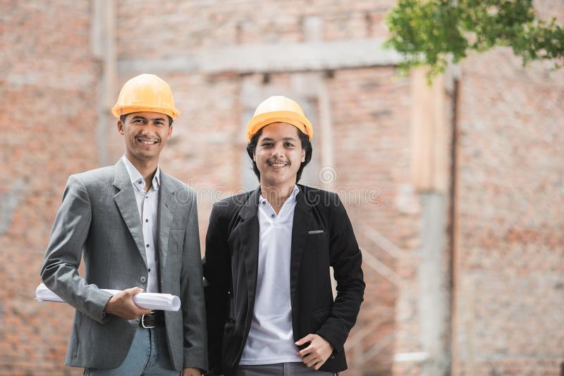 Arkitekt och byggmästare som framme står av oavslutat hus arkivbilder