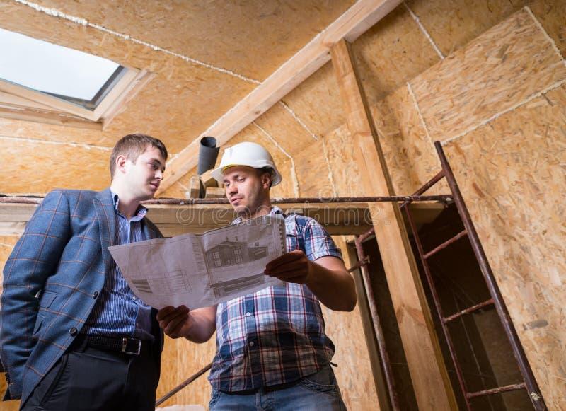 Arkitekt och ordförande Consulting Building Plans royaltyfri fotografi