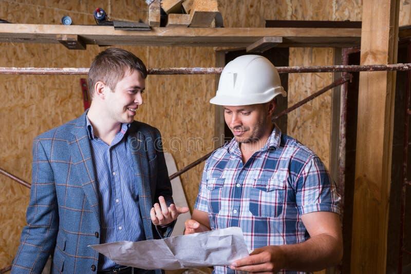 Arkitekt och ordförande Inspecting Building Plans fotografering för bildbyråer