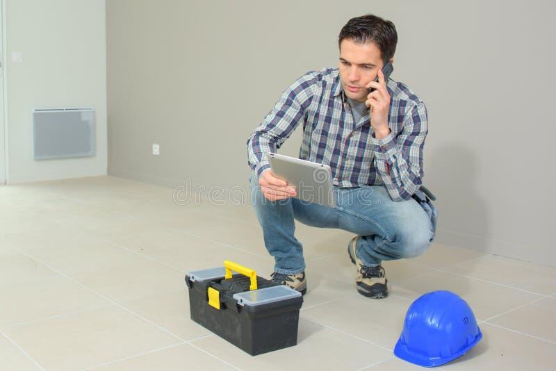 Arkitekt som arbetar på konstruktionsplatsen som talar på telefonen royaltyfri fotografi
