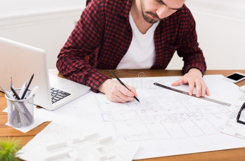 Arkitekt som i regeringsställning arbetar på ritning arkivbilder