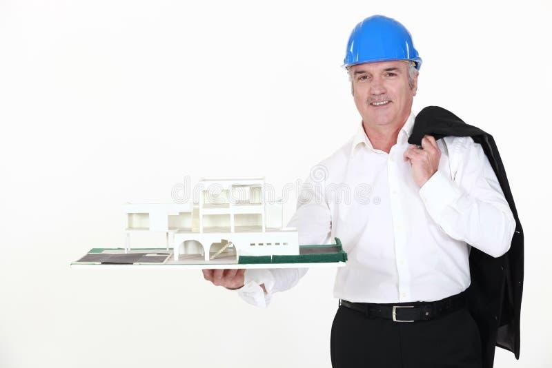 Arkitekt som rymmer ett miniatyrhus royaltyfria foton