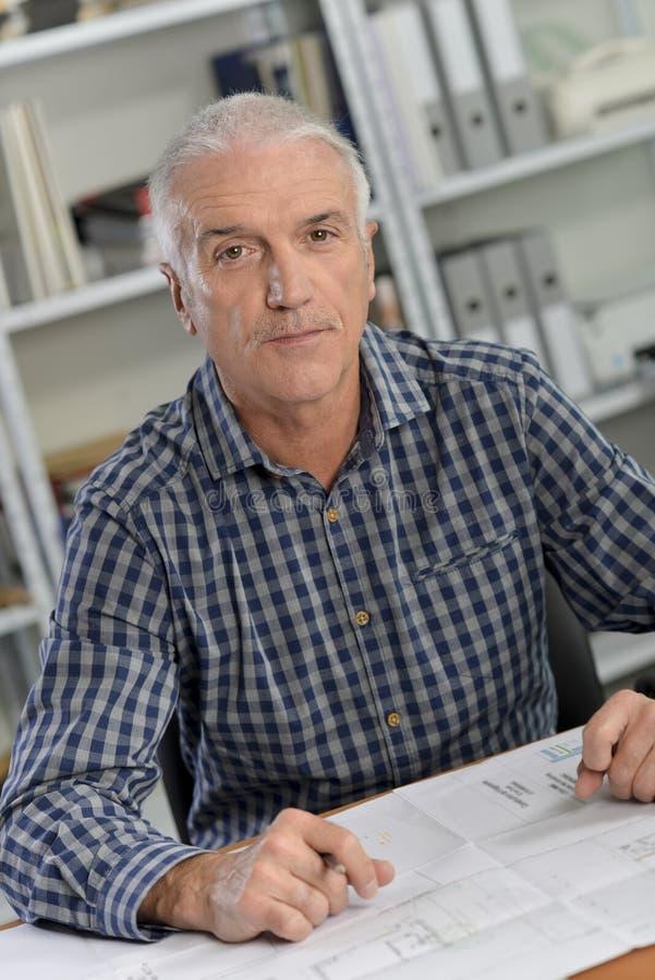 Arkitekt som sitts på skrivbordet med blåa tryck royaltyfria bilder