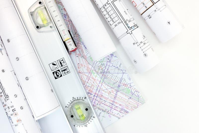 Arkitektarbetsplats med rullar av konstruktionsritningar, plan royaltyfri foto