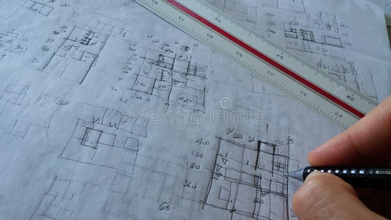 Arkitekten som arbetar med, skissar arkivbilder