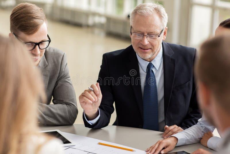 Arkitekter med minnestavlaPC och ritning på kontoret royaltyfria foton