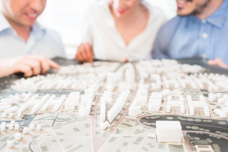 Arkitekter med modellen för stadsplanering royaltyfri foto