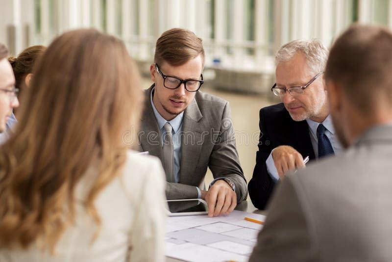 Arkitekter med ritning- och minnestavlaPC på kontoret arkivbilder