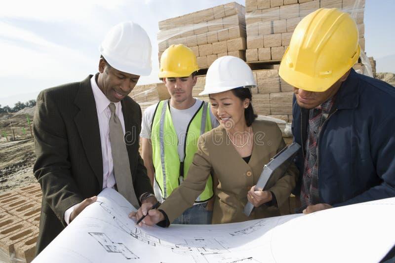 Arkitekter med ritningen på konstruktionsplatsen fotografering för bildbyråer