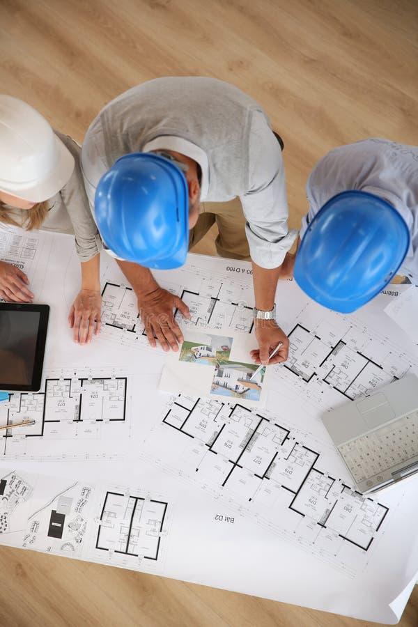 Arkitekter som arbetar med plan och datorer arkivfoto