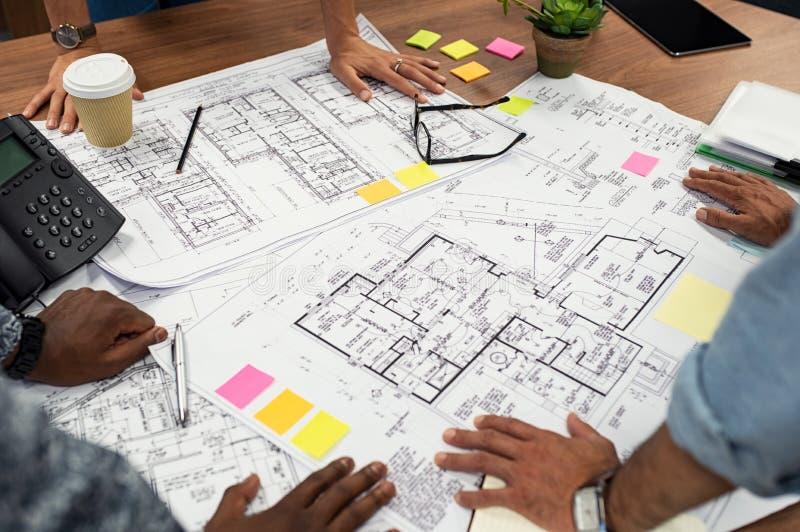 Arkitekter som arbetar på ritningar arkivfoto