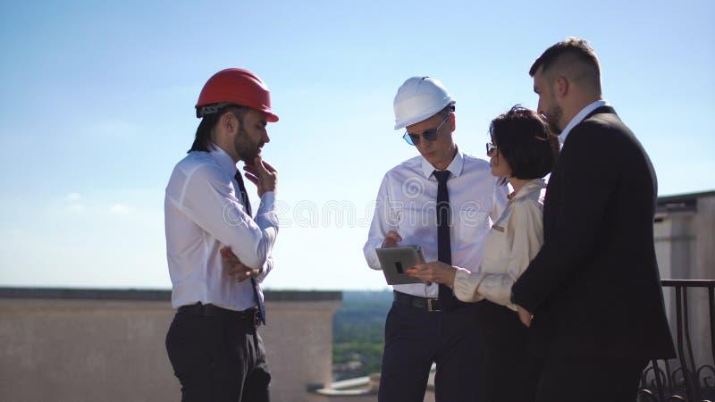 Arkitekter som diskuterar projekt på tak arkivfoton