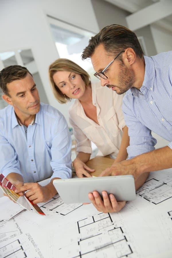 Arkitekter som möter och diskuterar konstruktionsplan royaltyfria bilder