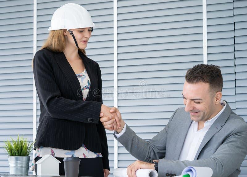 Arkitektkvinna med handskakningen med partnern arkivbild
