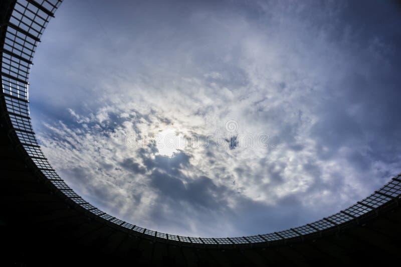 Arkitektonisk delstadion av en öppning för passerande mot den blåa himlen och molnen arkivbild