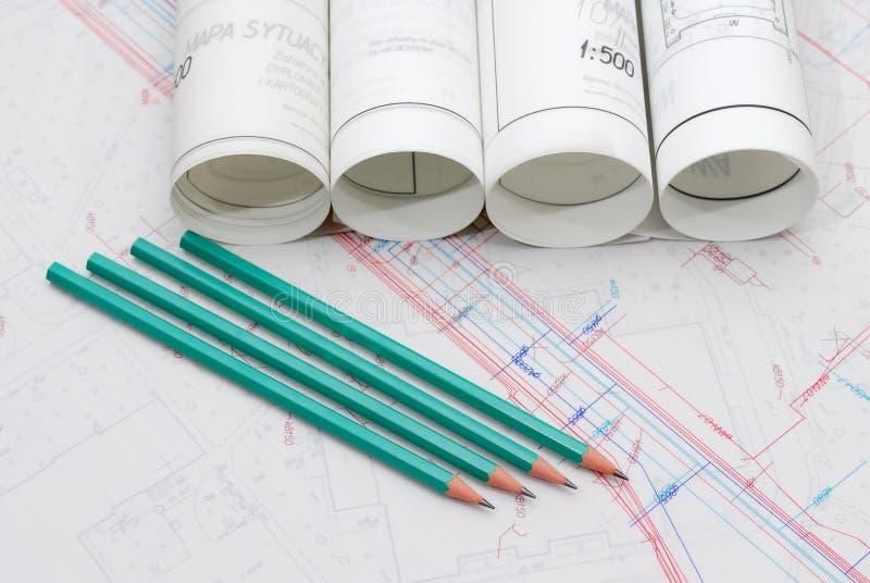 Arkitektoniska plan som ligger på ritbord royaltyfri foto