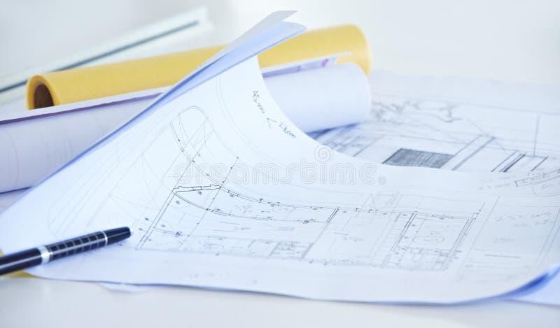 Arkitektoniska teckningar på skrivbordet arkivbild