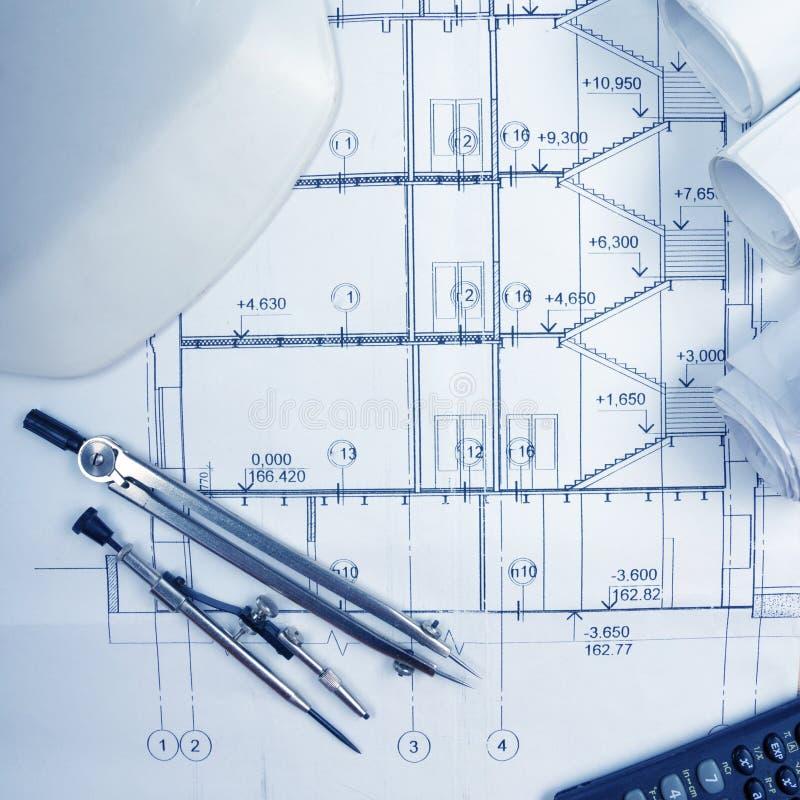 Arkitektoniskt projekt, ritningar, ritningrullar, kompassavdelare, räknemaskin, vit säkerhet på plan Iscensätta hjälpmedelsikten  royaltyfri fotografi