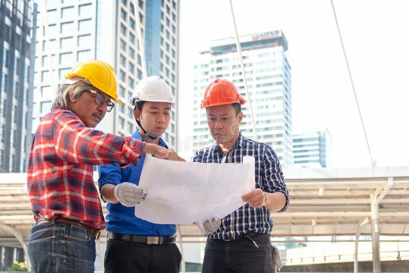 Arkitektteknikerlag som planerar det blåa trycket i konstruktionsstadsplats Arbetarsäkerhetskontroll royaltyfri fotografi