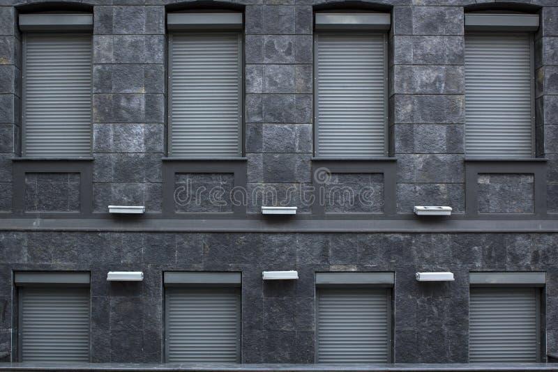 Arkitekturbyggnadsfasade från den gråa granitstenen med fönster som stängs med metallrollets fotografering för bildbyråer