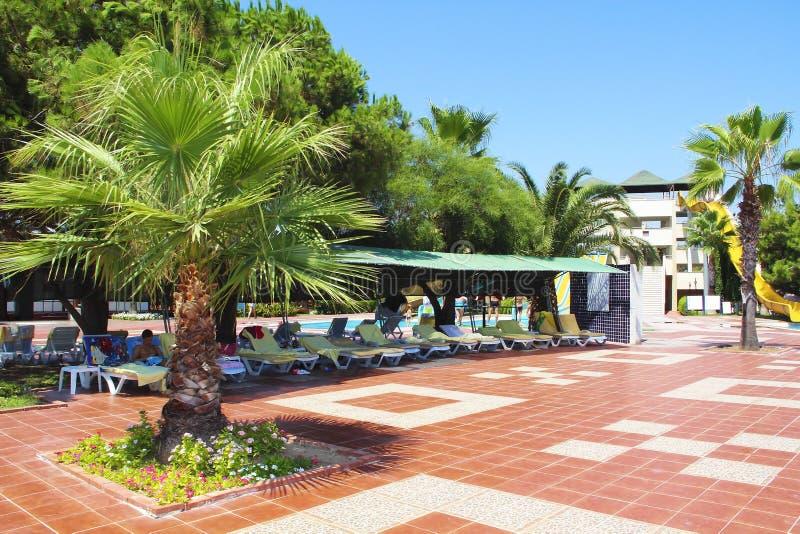 Arkitekturen av det turkiska hotellet med soldagdrivare, palmträd och folk som kopplar av i sommaren royaltyfria foton