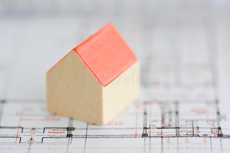 Arkitekturplan av en byggnad med den lilla modellen inhyser överst av ritningar royaltyfria foton