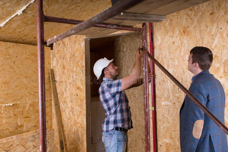 ArkitektWatching Worker Check nivåer på plats royaltyfri bild