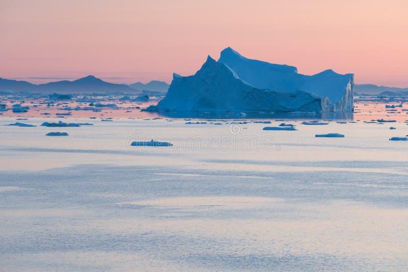 Arktiskt naturlandskap med isberg i Gr?nlandicefjord med solnedg?ng/soluppg?ng f?r midnatt sol i horisonten ovanf?r den h?rliga n royaltyfri fotografi