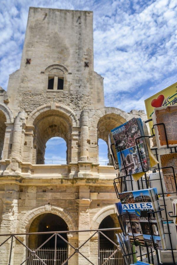 Tourists pass souvenir shops next to the Arenes d`Arles, Roman Amphitheater. Arles, France - June 16th, 2018: Tourists pass souvenir shops next to the Arenes d` royalty free stock photo