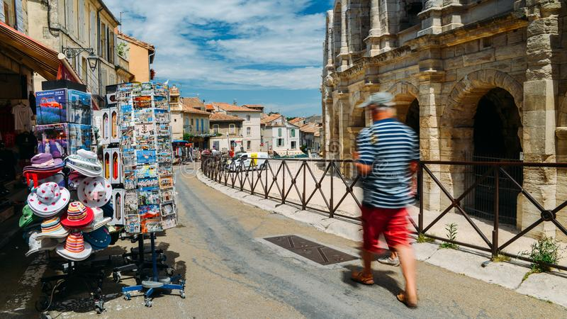 Tourists pass souvenir shops next to the Arenes d`Arles, Roman Amphitheater. Arles, France - June 16th, 2018: Tourists pass souvenir shops next to the Arenes d` stock photography