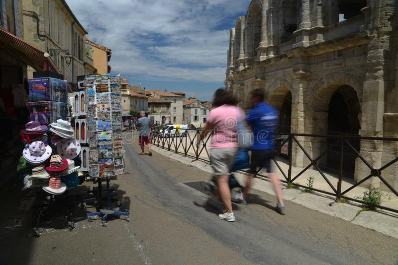 Tourists pass souvenir shops next to the Arenes d`Arles, Roman Amphitheater. Arles, France - June 16th, 2018: Tourists pass souvenir shops next to the Arenes d` royalty free stock photos