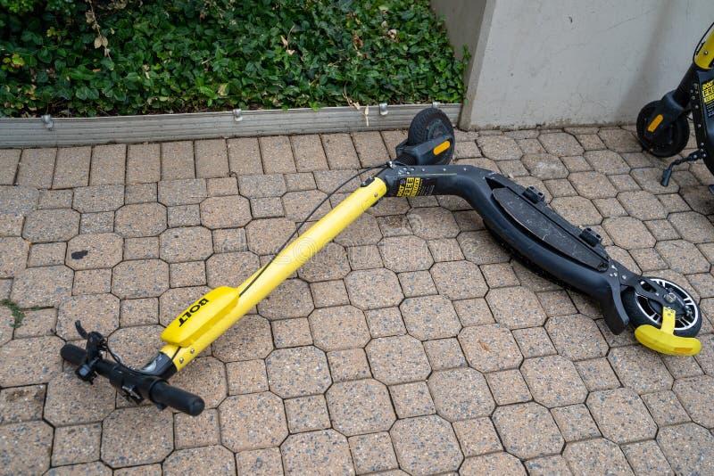Arlington, Virginia, 7 Agosto 2019: Uno scooter senza marca bolt è scaricato e caduto su un marciapiede, parcheggiato in modo imp immagine stock libera da diritti