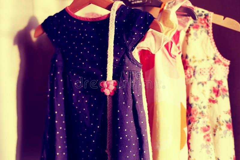Armário com os vestidos coloridos do bebê no gancho imagens de stock