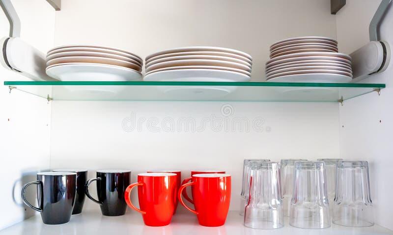 Armário da cozinha com placas, os copos e vidros disheslike imagens de stock