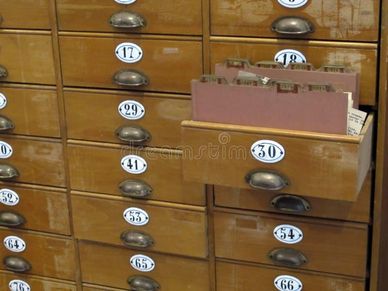 Armário de arquivo da biblioteca com as gavetas de cartão de madeira velhas fotos de stock