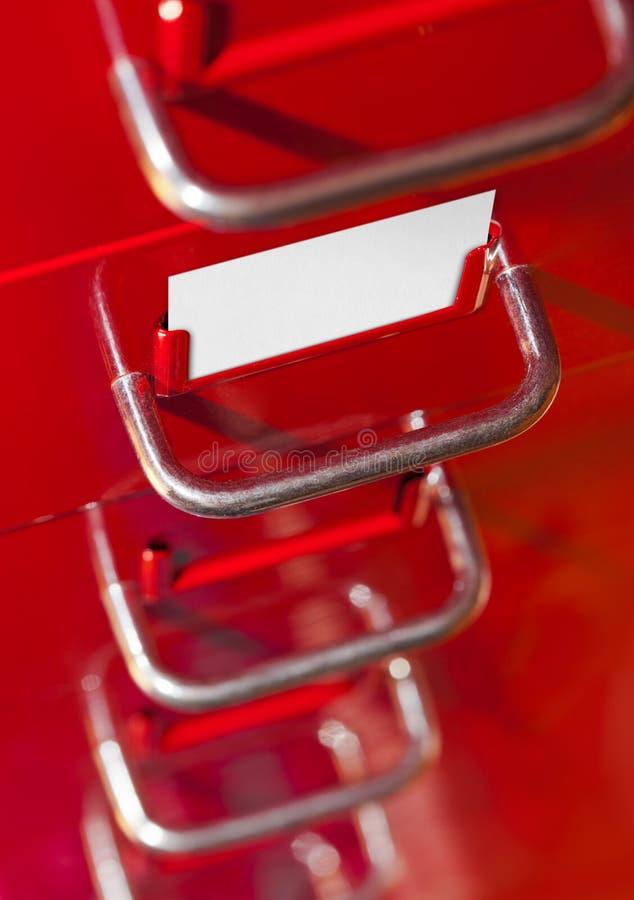 Armário de arquivo vermelho com cartão vazio foto de stock