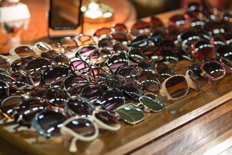 Armário de madeira antigo com uma coleção dos óculos de sol das mulheres do vintage na parte superior imagem de stock