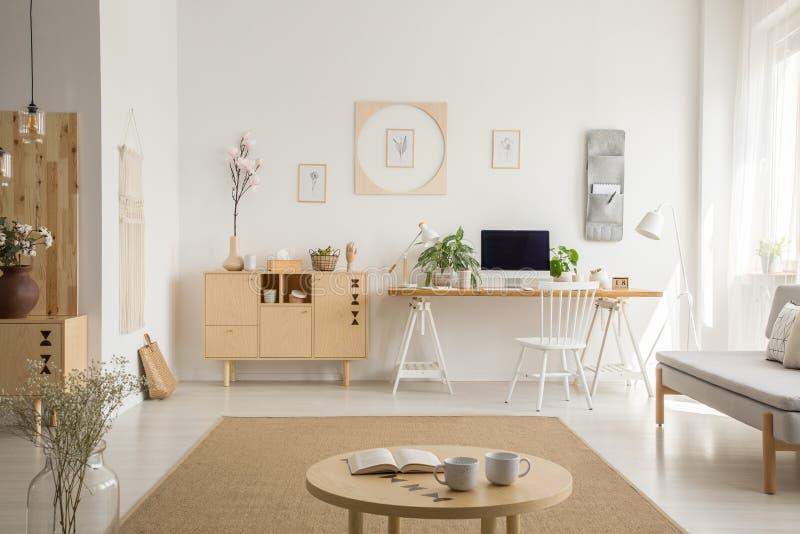 Armário de madeira ao lado da mesa no interior branco do escritório domiciliário com cartazes e plantas Foto real foto de stock royalty free