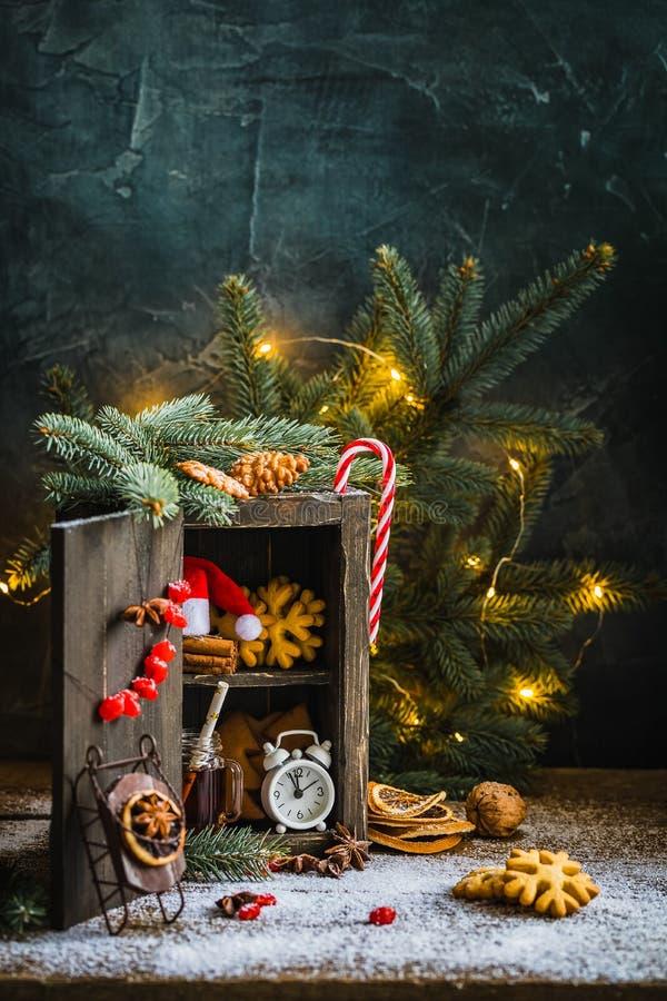 Armário de madeira mágico com cookies do pão-de-espécie, canela, despertador, caneca de chá, porcas e os arandos secados fotos de stock royalty free