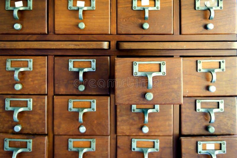 Armário de madeira velho da gaveta da medicina do vintage Armário de arquivo do catálogo imagem de stock