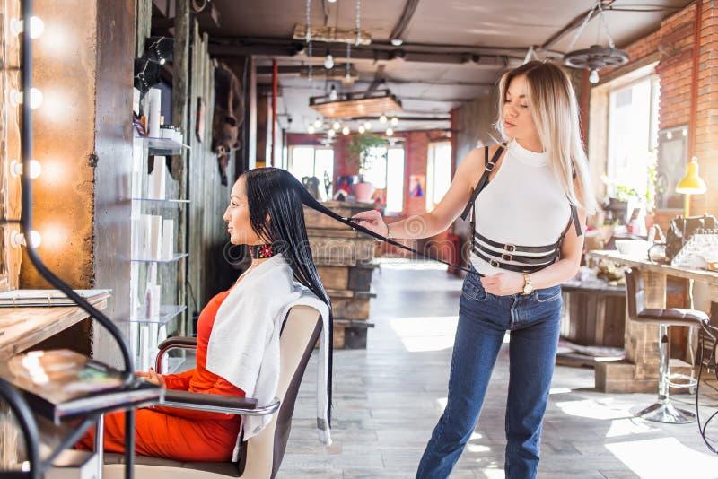 Armário fêmea do cabelo que trabalha em denominar um cabelo do ` s da mulher Cabeleireiro em um humor feliz fotografia de stock royalty free