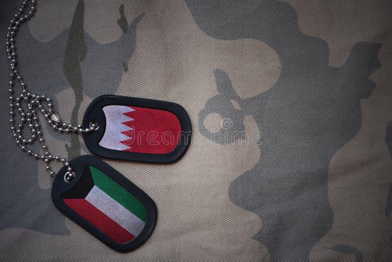 armémellanrum, hundetikett med flaggan av Bahrain och Kuwait på den kaki- texturbakgrunden fotografering för bildbyråer
